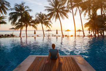 summer holiday getaway in luxury beach hotel, tourist relaxing near luxurious swimming pool at sunset, vacation on tropical island