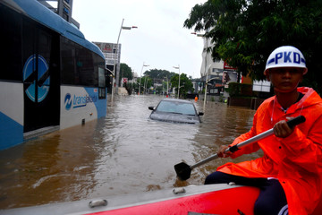 A security guard uses an inflatable boat as floods hit Kemang area in Jakarta