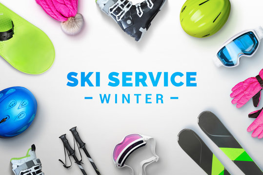 Ski service winter text surrounded by ski and snowboard equipment. Top view, flat lay