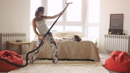 Photo on textile frame Dance School Young woman dancing with vacuum cleaner doing chores cleaning house having fun silly dance listening to music wearing headphones enjoying carefree weekend morning at home