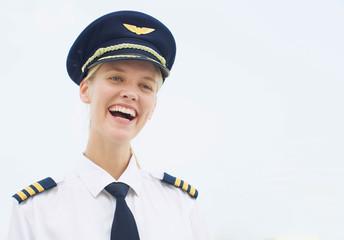 happy female pilot laughing in uniform. Professional pilot woman smiling at work.
