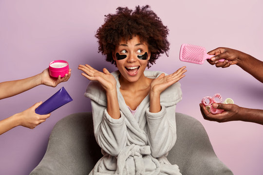 Beauty spa woman with Afro curly hairstyle, wears domestic clothes, poses on armchair, surrounded with humans hands holding cosmetic cream, haircomb and curlers, laughs from positive emotions