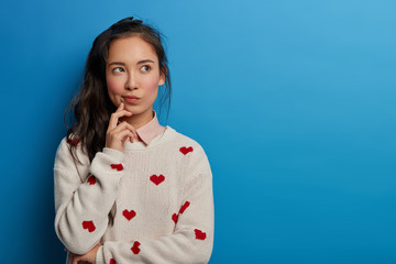 Contemplative pretty millennial young Asian woman looks away, builds plans in mind, has thoughtful face expression, long dark pony tail, wears sweater with hearts, isolated over blue background