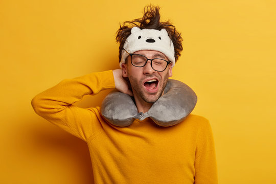 Sleepy male traveler yawns as wants to sleep, travels in transport with neck pillow, wears transparent glasses, headband, yellow jumper, poses indoor. People, tiredness and travelling concept