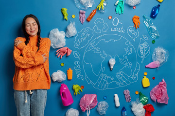 Poster de jardin Sous-marin Ethnic woman embraces herself with love, dressed in casual clothes, enjoys pleasant thoughts, thinks about volunteering work, stands against blue wall with symbolic picture of planet and garbage