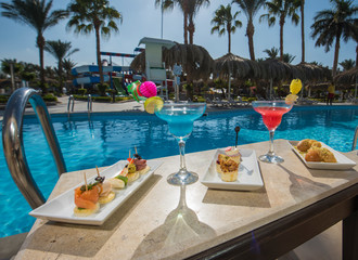 Cocktail drinks on table by a swimming pool of luxury hotel resort