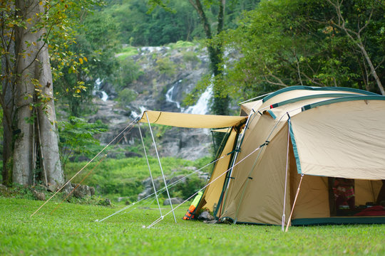 camping tent on waterfall and stream with tree in green jungle or forest for summer winter holiday relax and vacation travel trip with trekking and picnic on meadow grass at Khlong Nam Lai Waterfall