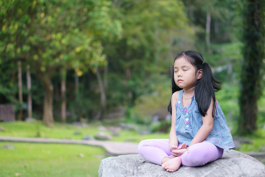 Asian child cute or kid girl close eye mindfulness meditating with breath and sit on stone or rock for peace and relax or yoga on nature green garden and tree at temple park or church outdoor