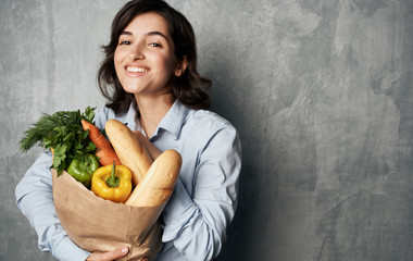 young woman holding shopping bag full of groceries