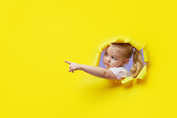 Little surprised child looking, peeping through the bright yellow paper hole. Showing hand to side. Advertise childrens goods. Copy space for text.