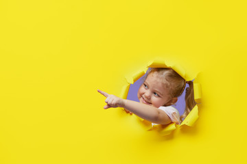 Fototapeta Little surprised child looking, peeping through the bright yellow paper hole. Showing hand to side. Advertise childrens goods. Copy space for text.