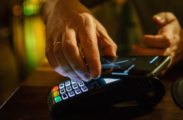 Contactless mobile payment. Payment terminal and smartphone in hands in bar