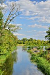 Fototapeta Ujście kanału wodnego do rzeki wśród drzew i chmur na niebie w letni dzień. obraz