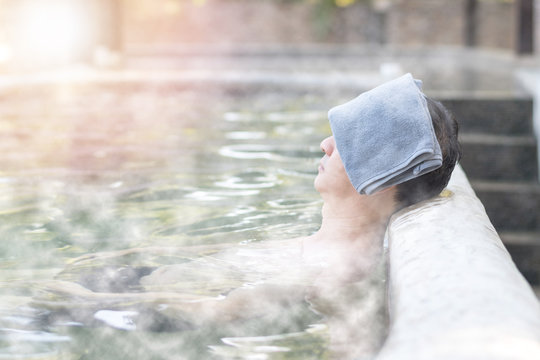 Nature Hotsping ans onsen travel tourism concept. Asia man relax in natural hot spring water pool during vacation.