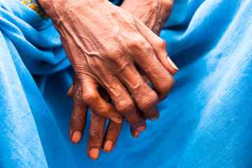 Hands of an old rustic indian woman in a blue sari