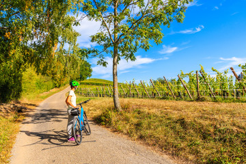 Young woman cycling on road along vineyards from Riquewihr to Hunawihr village, Alsace Wine Route, France