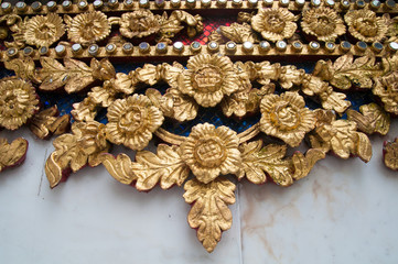 Traditional wood carving with ancient flower patterns decorating with gold mirror, Thailand
