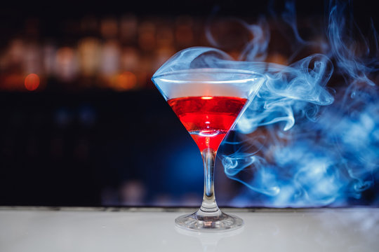 Red cocktail in martini glass with smoke, bartender drinks concept