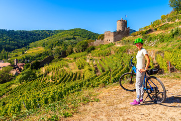 Young woman posing with bicycle among vineyards and view of Kaysersberg castle, Alsace Wine Route, France