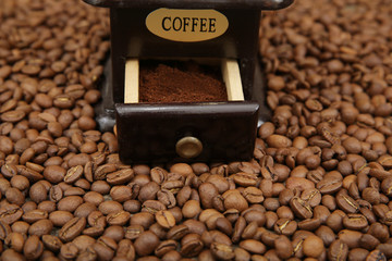wooden coffee grinder and beans and ground coffee on beans background. Close-up.