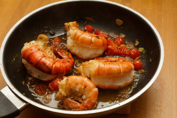 King prawns in a pan with tomatos and herbs