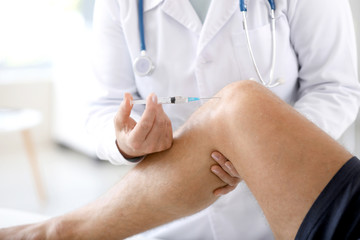 Doctor giving sportsman with joint pain injection in clinic, closeup