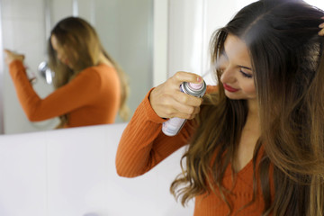 Young woman applying dry shampoo on her hair. Fast and easy way to keep hair clean with dry shampoo. Focus on the hand with spray.