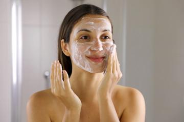Fototapeta Skincare woman washing face  foaming soap scrubbing skin. Face wash exfoliation scrub soap woman washing scrubbing with skincare cleansing product. Enjoying relaxing time. obraz