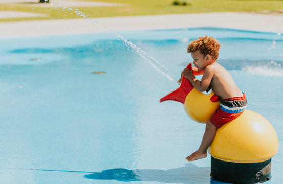 Adorable african baby boy playing on water playground on a hot summer day