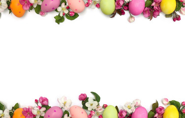 Easter decoration. Easter frame of pink flowers apple tree and colored easter eggs on white background with space for text. Top view, flat lay