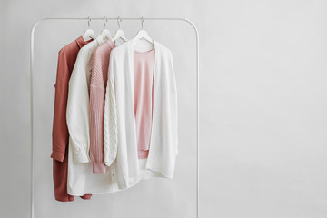 Feminine clothes in pastel pink  color on hanger on white background.  Elegant dress,  jumper, shirt and other fashion outfit. Spring cleaning home wardrobe. Minimal concept. Wall mural