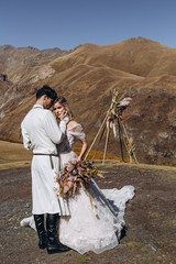 young, stylish, loving brides posing for a photo on an incredibly beautiful background of the Caucasus Mountains: hugging, kissing, laughing, and rejoicing in the happiest day of their lives