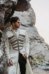 noise effect, selective focus: stylish Georgian man dressed in white national men's suit. Portrait of Georgian groom during wedding on Caucasus mountains