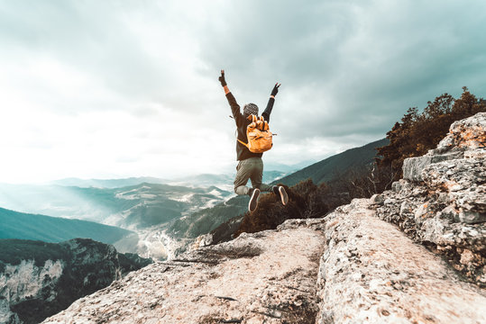 Young man traveler jumps on a background of mountain raising arms to the sky