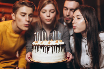 a charming woman blows out candles on a cake after making a wish on her birthday. The company of best friends came to congratulate the girlfriend on holiday