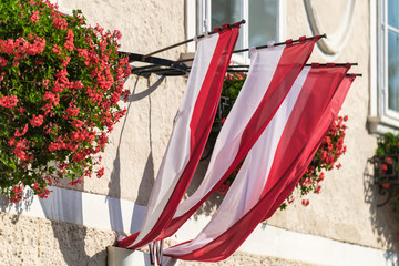 Bright facade of a residential house with red colorful flowers and the austrian flag