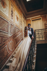 stylish wedding couple of pretty bearded groom and elegant blonde woman in wedding dress posing for photo in chic palace, copy space, noise effect