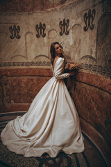 exquisite bride with perfect makeup and beautiful white wedding dress posing for a photo in a romantic dark interior