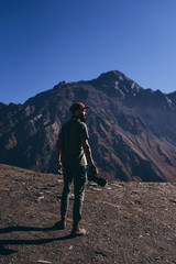 stylish bearded man with camera in hands on top of Georgian mountains: nature photographer traveler taking photo of beautiful landscape from top of the mountain
