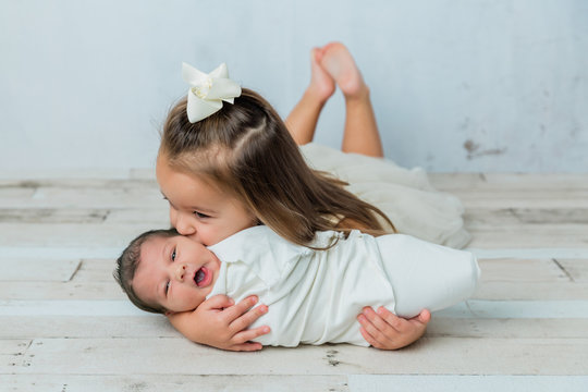 3 year old big sister kissing her newborn little sister in a cool tone white room