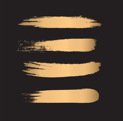 Set of gold paint brush strokes isolated on black background. Vector illustration