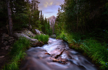 Long exposure of a river in the Rocky Mountains at sunset. There are pine trees lining the river and a mountain peak can be seen in the distance.