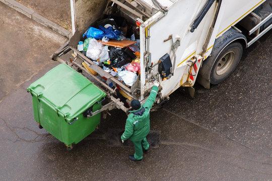 Garbage man operating garbage truck in residential area