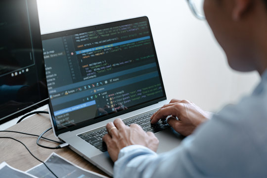 Programmer Typing Code on desktop computer, Developing programming and coding technologies concept.
