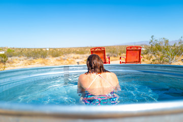 A girl in her twenties comes up for air after refreshing in a small outdoor tub pool in Joshua Tree, California