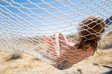 A girl in a bikini relaxes in a hammock in the middle of the desert