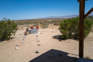 A woman relaxes in a stock tank basin with a hose in an empty desert in Joshua Tree, CA