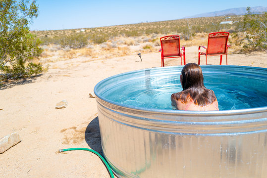 A girl comes up for air after refreshing in a small outdoor tub pool in Joshua Tree, California