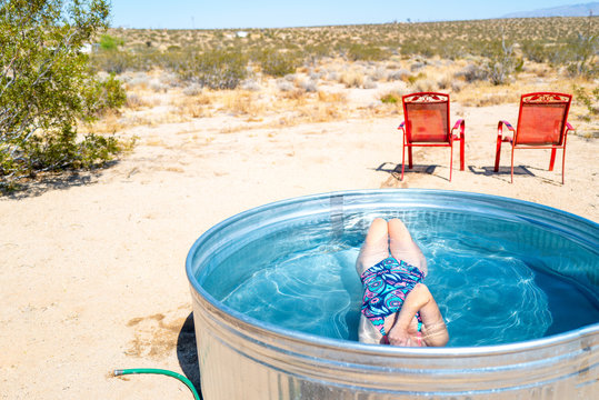 A girl submerges underwater in a small outdoor tub pool