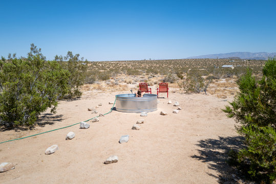 A woman relaxes in a stock tank pool with a hose in an empty desert in Joshua Tree, CA